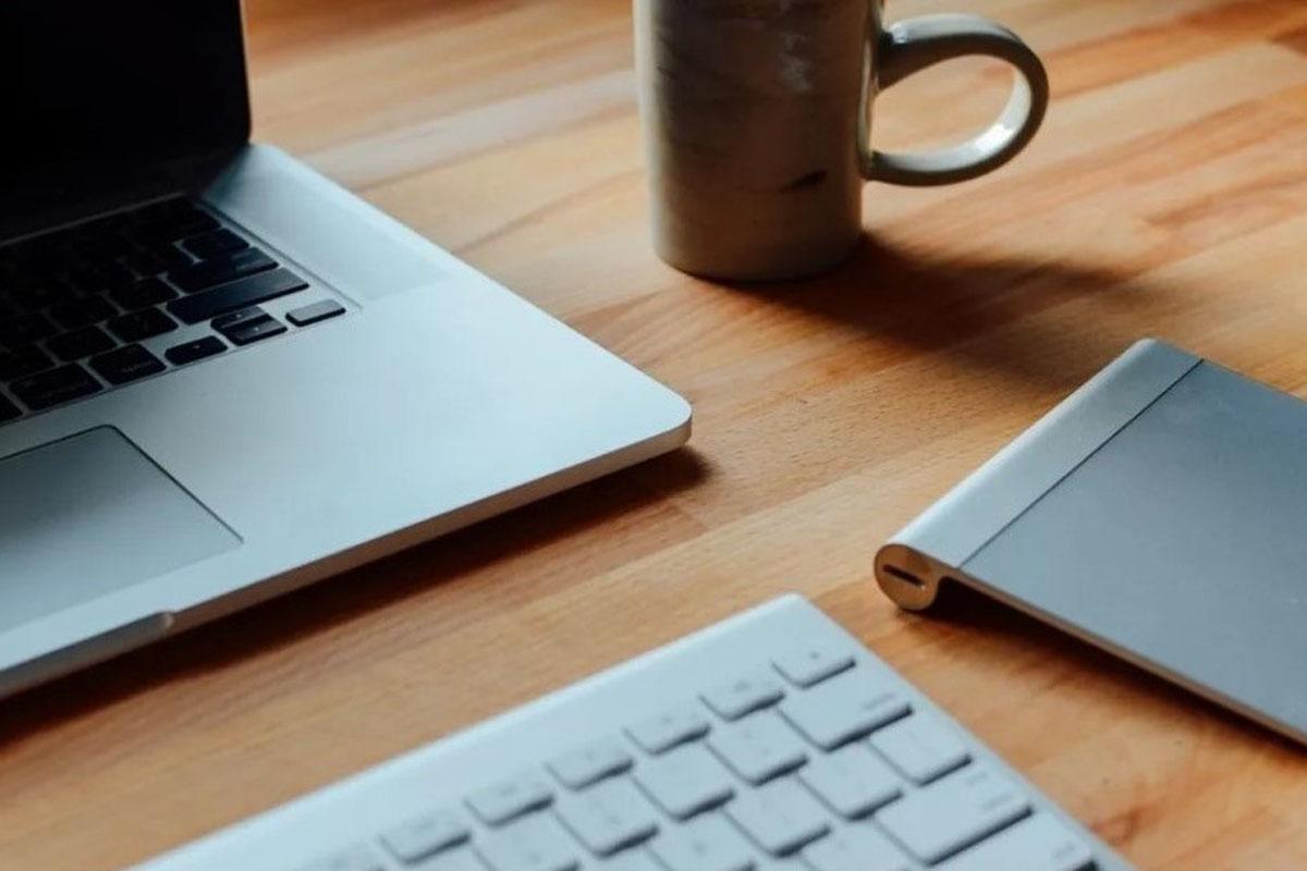 Laptop und Kaffeetasse auf Schreibtisch